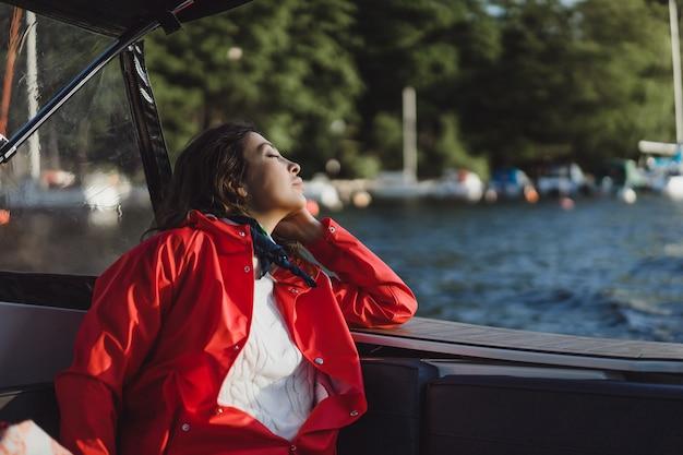Mulher jovem e bonita em uma capa de chuva vermelha monta um iate privado. estocolmo, suécia