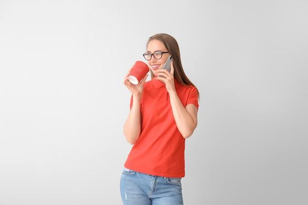 Mulher jovem e bonita em uma elegante camisa pólo e com café falando ao telefone