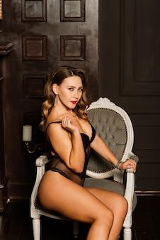Mulher jovem e bonita em uma lingerie preta sexual, posando com decorações de natal
