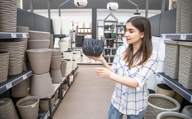 Mulher jovem e bonita em uma loja de flores escolhe um vaso de flores.