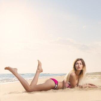 Mulher jovem e bonita em uma praia de areia do oceano em um maiô ao pôr do sol