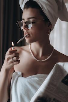 Mulher jovem e bonita em uma toalha fuma um cigarro e lê jornal