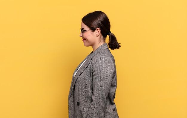 Mulher jovem e bonita em vista de perfil, olhando para copiar o espaço à frente, pensando, imaginando ou sonhando acordada