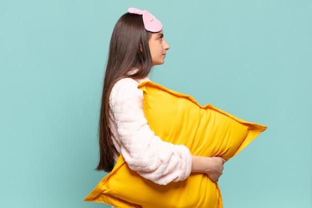 Mulher jovem e bonita em vista de perfil, olhando para copiar o espaço à frente, pensando, imaginando ou sonhando acordado. acordar de pijama conceito