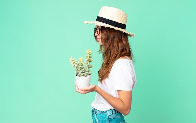 Mulher jovem e bonita em vista de perfil pensando, imaginando ou sonhando acordada com um chapéu de palha e segurando um cacto
