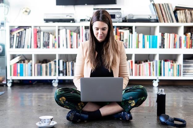 Mulher jovem e bonita empreendedora usando um laptop enquanto está sentado no chão de casa.