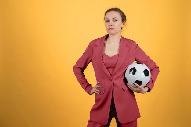 Mulher jovem e bonita empresária com bola de futebol posando em fundo amarelo.