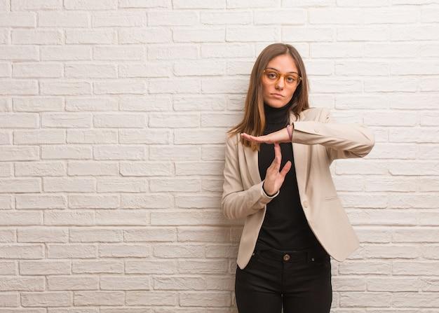 Mulher jovem e bonita empresária fazendo um gesto de tempo limite