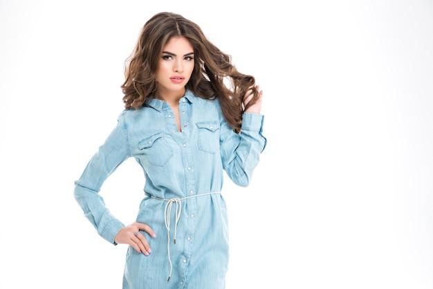 Mulher jovem e bonita encantadora com camisa jeans longa em pé e tocando o cabelo na parede branca
