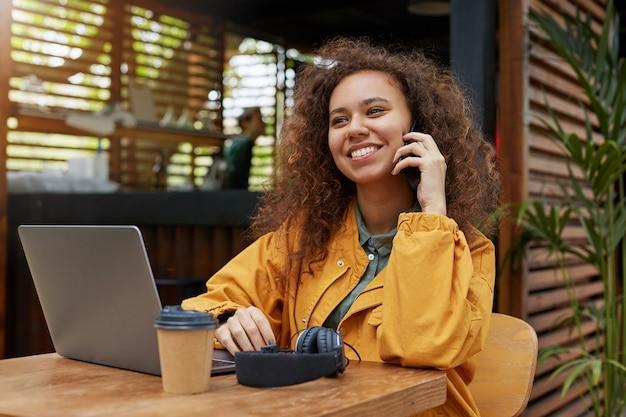 Mulher jovem e bonita encaracolada de pele escura situada no terraço de um café, vestindo um casaco amarelo, bebendo café, trabalha em um laptop, sorrindo e falando ao telefone com um amigo.