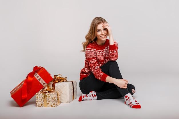 Mulher jovem e bonita engraçada com uma camisola vintage vermelha sentada perto dos presentes