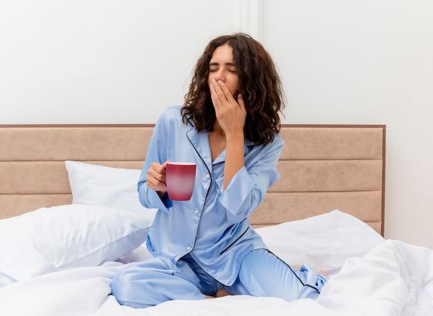 Mulher jovem e bonita engraçada de pijama azul, sentada na cama com uma xícara de café, acordando bocejando, sentindo cansaço matinal no interior do quarto