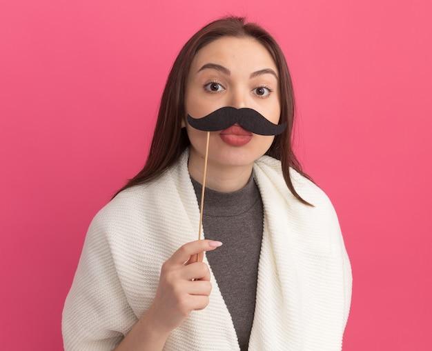 Mulher jovem e bonita engraçada segurando um bigode falso acima dos lábios com os lábios franzidos, isolados na parede rosa