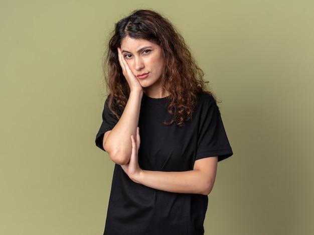 Mulher jovem e bonita entediada mantendo a mão no rosto, olhando para a frente, isolada na parede verde oliva com espaço de cópia