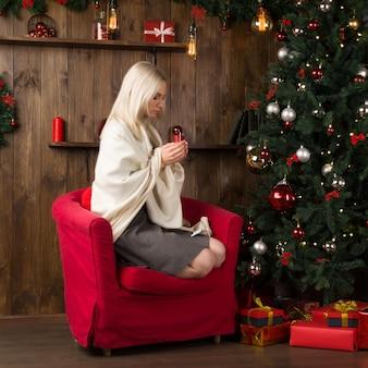 Mulher jovem e bonita envolta em uma manta se senta em uma cadeira vermelha com uma xícara de chá ou café no interior da casa de ano novo, perto da árvore de natal. - imagem