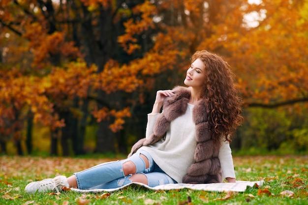 Mulher jovem e bonita esbelta com um colete de pele descansando no outono no parque e sentada no gramado