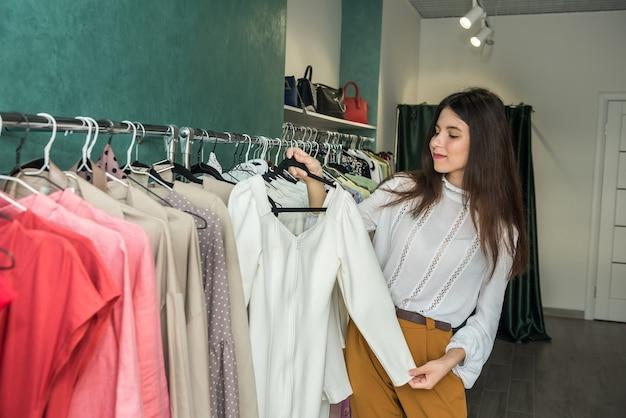 Mulher jovem e bonita escolhendo a jaqueta na loja de roupas. novo estilo