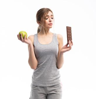 Mulher jovem e bonita escolhendo entre alimentos saudáveis e não saudáveis
