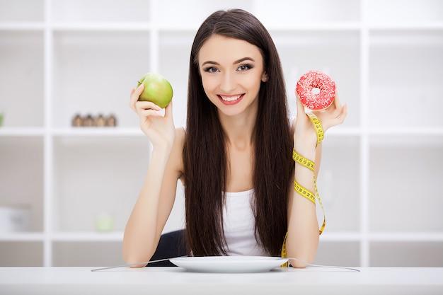 Mulher jovem e bonita escolhendo entre comida saudável e junk food