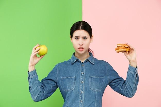 Mulher jovem e bonita escolhendo entre frutas e fast-food unhelathy no estúdio.