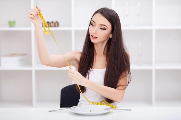 Mulher jovem e bonita escolhendo entre frutas e junk food