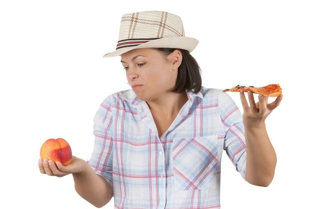 Mulher jovem e bonita escolhendo uma fatia de pizza ou pêssego fresco em um fundo branco