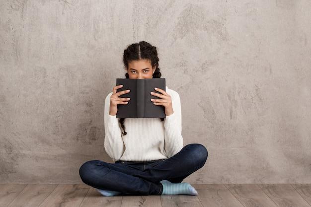 Mulher jovem e bonita escondendo a boca atrás de livro sobre parede bege