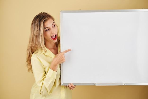 Mulher jovem e bonita espantada apontando para um quadro branco vazio, conceito de educação
