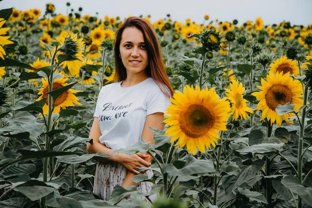 Mulher jovem e bonita está de pé em girassóis florescendo olhando