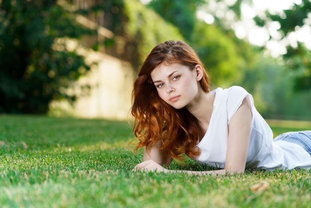 Mulher jovem e bonita está descansando na grama verde fresca