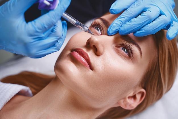 Mulher jovem e bonita está evitando o envelhecimento visitando um cosmetologista e aplicando injeções de botox no rosto
