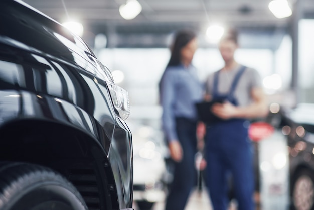 Mulher jovem e bonita está falando com o mecânico de carro bonito enquanto repara um carro na concessionária