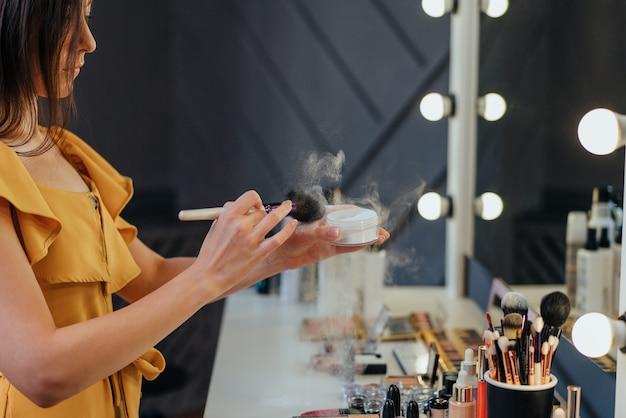 Mulher jovem e bonita está fazendo maquiagem usando um pó enquanto olha para o espelho