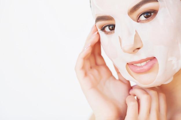 Mulher jovem e bonita está ficando máscara de argila facial no spa, deitado com pepinos nos olhos