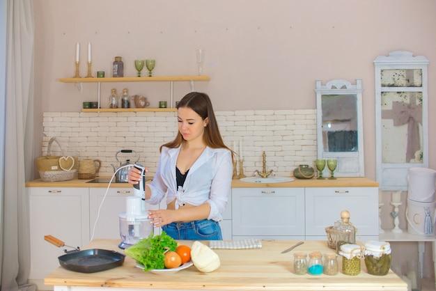 Mulher jovem e bonita está preparando salada de legumes na cozinha. alimentos saudáveis. salada vegan.