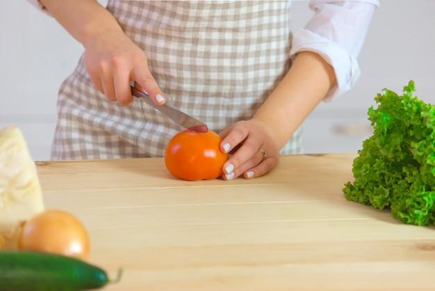 Mulher jovem e bonita está preparando salada de legumes na cozinha. comida saudável. conceito de dieta. estilo de vida saudável. cozinhando em casa. preparar comida. cortando ingredientes na mesa