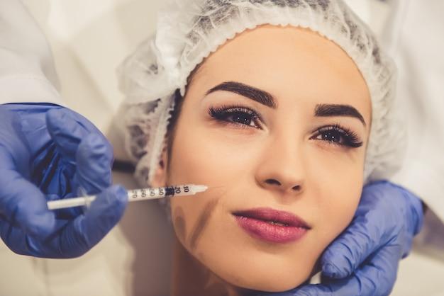 Mulher jovem e bonita está recebendo uma injeção no rosto.