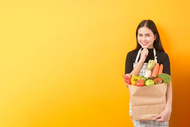 Mulher jovem e bonita está segurando legumes na sacola de compras em fundo amarelo studio