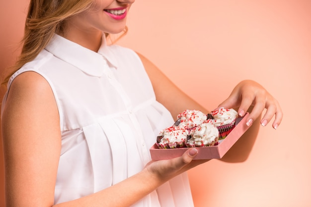 Mulher jovem e bonita está segurando uma caixa com bolos.