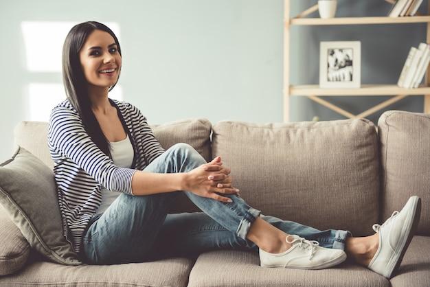 Mulher jovem e bonita está sorrindo enquanto está sentado no sofá