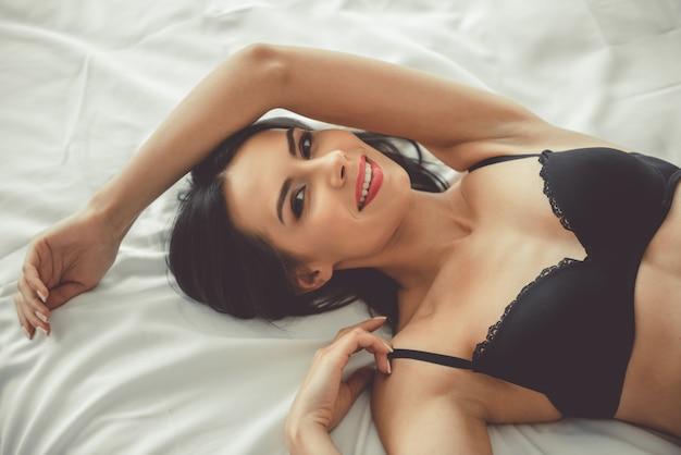 Mulher jovem e bonita está sorrindo enquanto estava deitado na cama