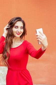 Mulher jovem e bonita está tomando selfie com smartphone em fundo laranja.