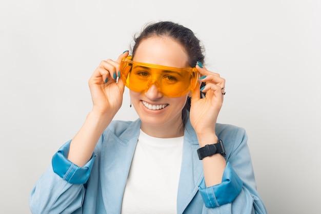 Mulher jovem e bonita está usando um par de óculos de proteção laranja.