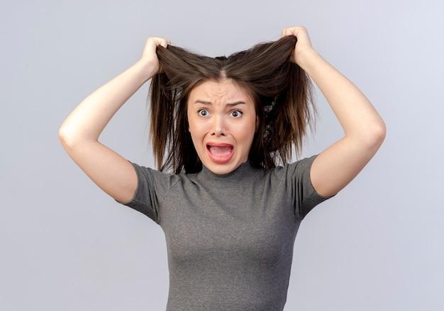 Mulher jovem e bonita estressada olhando em linha reta puxando o cabelo dela, isolado no fundo branco