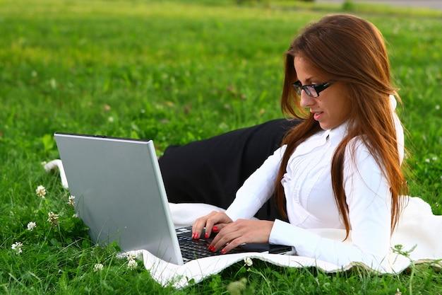 Mulher jovem e bonita estudando no parque