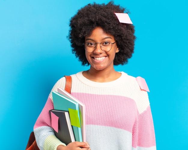 Mulher jovem e bonita estudante afro segurando cadernos