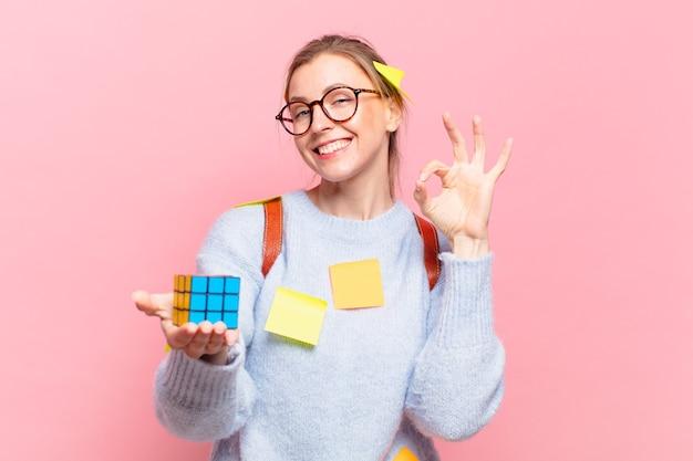 Mulher jovem e bonita estudante com expressão feliz e segurando um objeto de desafio de inteligência