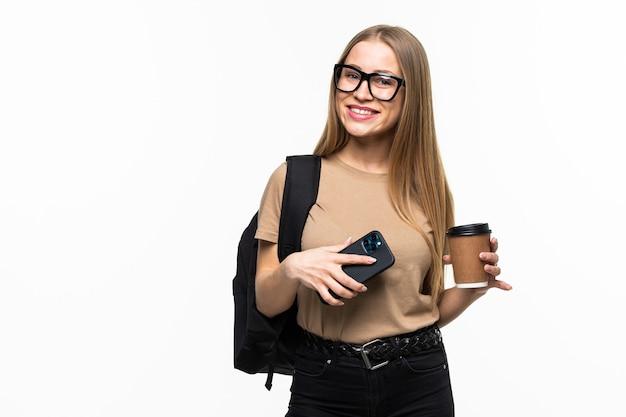 Mulher jovem e bonita estudante com telefone inteligente e café com mochila isolada na superfície branca
