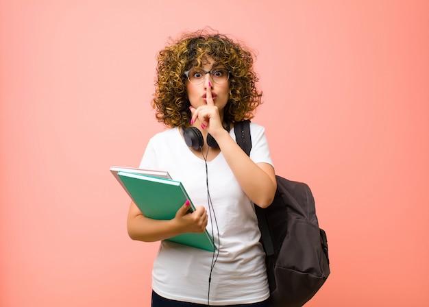 Mulher jovem e bonita estudante pedindo silêncio e sossego, gesticulando com o dedo na frente da boca, dizendo shh ou mantendo um segredo contra a parede rosa