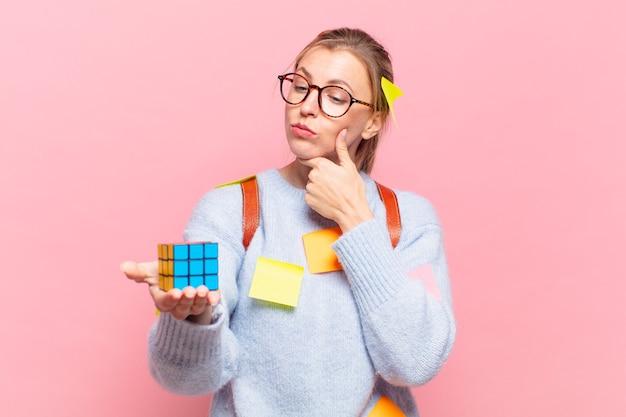 Mulher jovem e bonita estudante pensando em expressão e segurando um objeto de desafio de inteligência